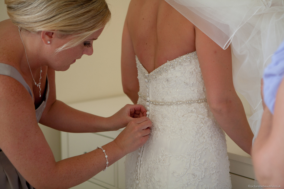 buttoning-up-the-wedding-dress-by-picture-me-beautiful-photography-uk